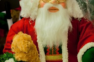Close-up of Christmas Santa Clause holding a teddy bear