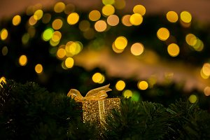 Beautiful golden gift decorated on Christmas tree blurred in gold bokeh background - selective focus