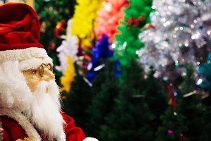 Santa Claus doll on various colors of Christmas trees background with copy space