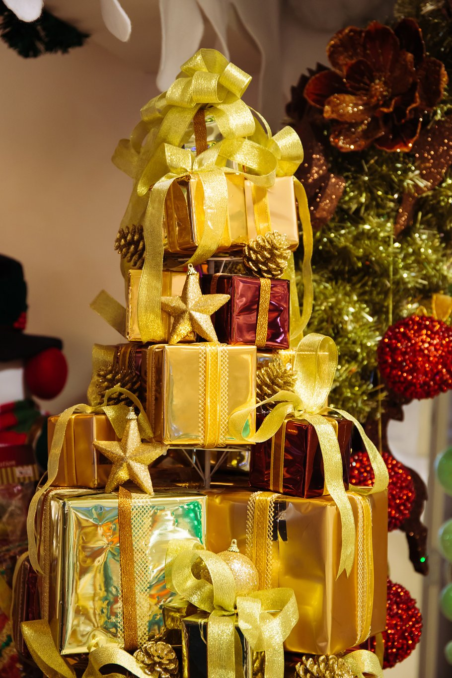 pile of shiny gift boxes decorated in christmas tree with christmas ornament decorations in the background
