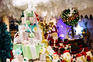 Pile of gift boxes decorated in Christmas tree with santa claus and Christmas ornament decorations in the background