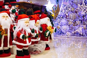 Group of Santa Claus dolls and snowman dolls with lighting decorated Christmas tree background with copy space