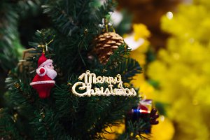 Merry Christmas text sign ornament attached on Xmas tree - selective focus.