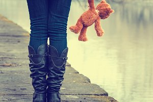 Sad lonely girl with teddy bear