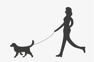 Silhouette of woman walking a dog.