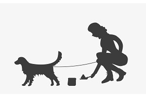 Silhouette of woman cleaning after a golden retriever dog.