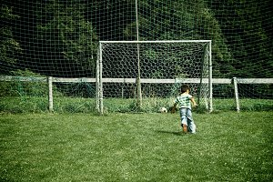 A boy is playing soccer