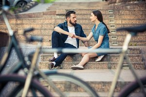 Young couple sitting opposite  a bicycle