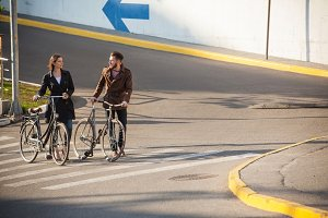 Young couple with a bicycle opposite city