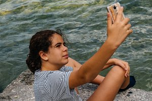 Beautiful girl sitting by the lake taking a selfie