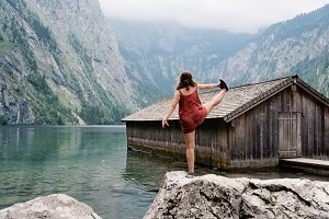 Girl standing on top of a rock and wooden cottage in beautiful l