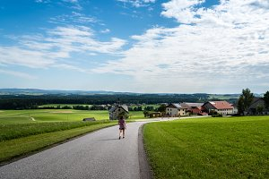 Scenic view of girl walking down a road in a green valley