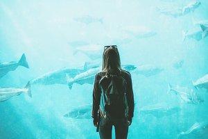Woman looking at fish in aquarium
