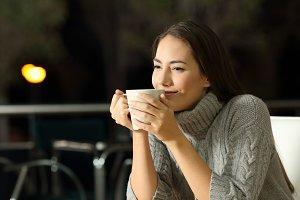 Pensive woman enjoying coffee