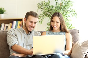Young happy couple using a laptop