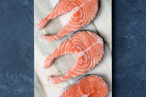 Uncooked salmon steaks on marble background. Top view