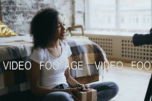 Attractive african girl recording video blog about packing christmas gift box at home