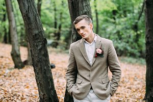 Young handsome man, standing near the tree. Autumn wedding. Soft focus