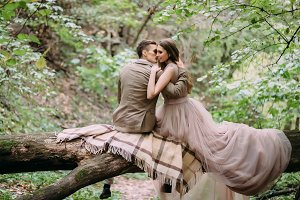 Stylish newlyweds having rest on a plaid in the forest. The bride and groom sits on the log in nature.
