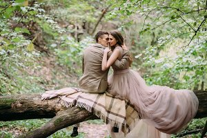 Romantic couple is gently hugs on the log. Autumn wedding