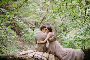 Newlyweds is tenderly hugging on a plaid in the forest. The bride and groom sits on the log in nature. Autumn wedding