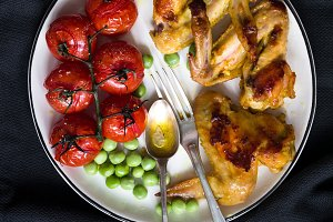 Chicken wings, roasted cherry tomato and green peas on white plate, healthy dinner meal
