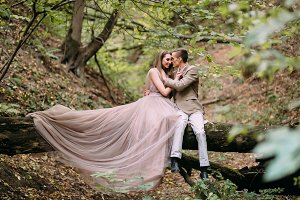 Newlyweds is tenderly hugging in the forest. Bride in beautiful long dress sits on the log in forest. Autumn wedding