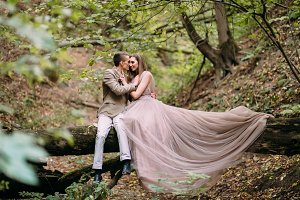 Newlyweds is tenderly hugging on a plaid in the forest. Bride in beautiful long dress sits on the log in forest.
