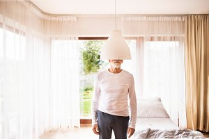 Senior man standing behind pendant lamp at home.
