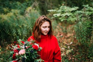 Beautiful young woman with rustic flowers. Happy girl smiling and holding bouquet outdoors. Autumn portrait of female in park.