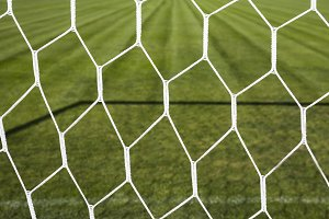 goal net and green soccer pitch