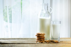 Chocolate chip cookies, bottle and glass of milk on wooden table near window, white background. Sunny morning, copy space