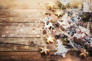 Christmas wreath with ginger cookies, silver stars, cones, hazelnut, anise, tape, ribbon, snowflakes, reindeer. Top view, copy space, light bokeh, snow effect, toned