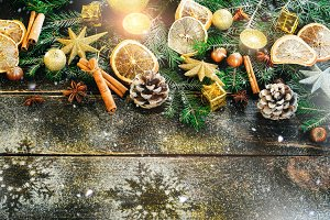 Christmas greeting card with gifts, candle, cones, cinnamon sticks, dry orange, green tree over old dark wood background. Top view with copy space for you text. Snow and bokeh