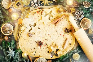 Ginger Bread Cookies. Christmas background with gifts, candle, cones, cinnamon sticks, dry orange, green tree fir branch, dough, rolling pin. Copy space.