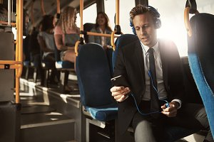 Young businessman listening to music on his morning commute