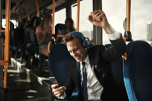 Young businessman reading texts and celebrating during his morning commute