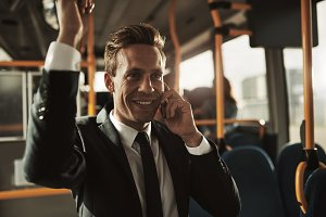 Smiling young businessman standing on a bus talking on his cellphone