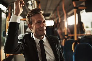 Smiling businessman standing on a bus during his morning commute