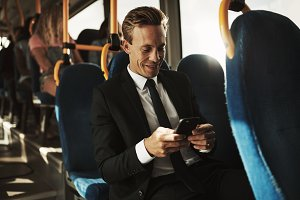 Smiling young businessman sitting on a bus reading text messages