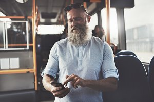 Smiling man with a beard sending texts on the bus