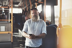 Mature man with a beard reading texts on the bus