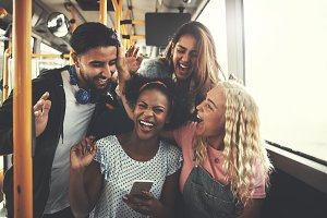 Smiling diverse friends using a cellphone together on the bus