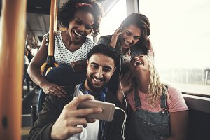 Smiling friends listening to music together on a bus