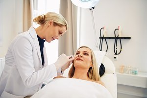 Doctor doing botox injections on a mature client's face