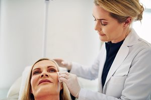 Doctor prepping the face of a woman for botox injections