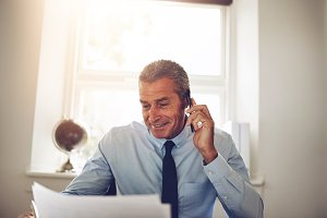 Smiling businessman discussing paperwork over the phone in his office