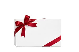 The white box wrapped with red ribbon with a bow