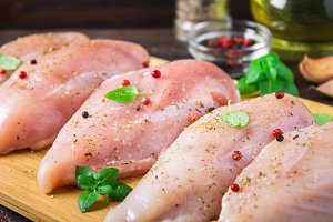 Raw chicken fillets on a cutting board against the background of a wooden table. Meat ingredients for cooking.