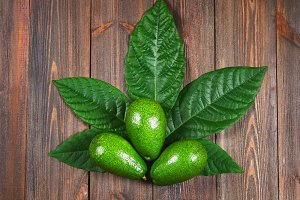 Three green raw ripe avocados with leaves lie in the form of cannabis on a wooden brown table. Top view.